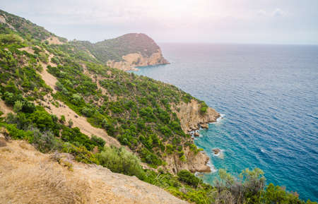 Epic view of greek coast from above with a blue turquoise water green bushes on cliffs and a beautiful sun on the horizon on a sunny summer day suited for a wallpaper