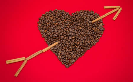 Coffee love suggested by a heart made from coffee beans and an arrow made from cinnamon sticks on a red romantic background