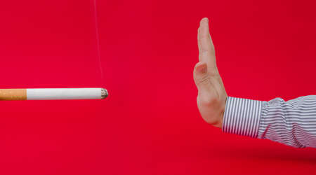 suggested: Say no to smoking suggested by a business man refusing a giant lit smoking cigarette trying to loose weight and cut off an unhealthy habbit on a red dangerous serious alerted background Stock Photo