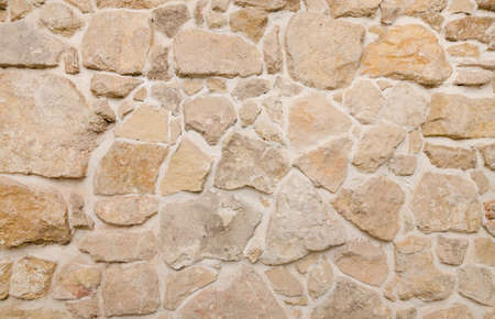 fortify: Ancient river stone wall texture with a warm look