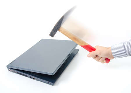 hit tech: Destroying an old laptop suggesting data hack, old technology, slow computer, data protction and pc repairman Stock Photo