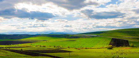 Green farm land view on hills with mountains at the horizon during a cloudy sunny spring day with highlited and shaded areas a blue cloudy sky sheep and a vibrant look Stock Photo