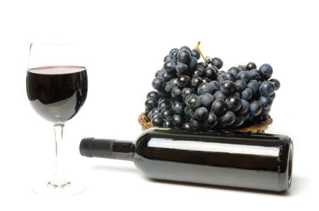 Red wine glass with bottle and grapes next to it Stock Photo