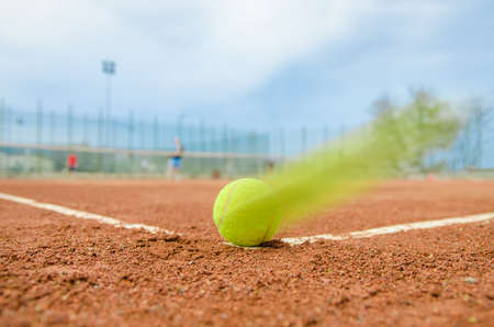 Tennis ball speeding on the corner line during a double match on a cloudy day