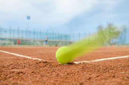 Tennisbal hard rijden op de hoek lijn tijdens een dubbele wedstrijd op een bewolkte dag