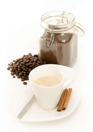 Hot coffee espresso in a white cup with cinamon coffee beans and a jar of grinded coffee on the background with portrait orientation