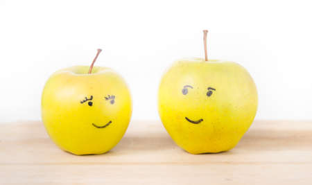 he she: Two yellow green apples in love looking at each other one being a male and the other a female or she apple and he apple on a wood cutting board Stock Photo