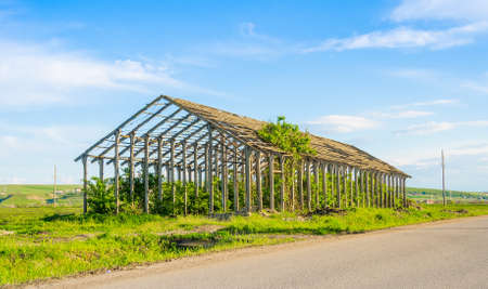 Abandoned wrecked and ruined agriculture structure still standing on farmland made of concrete and steel beams suggesting good building and engineering Stock Photo