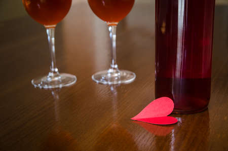 A red love heart with a rose wine bottle and two glasses on the background on a wood table suggesting romance and emotions in a warm light