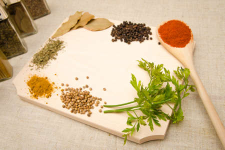 Herbs and spices on a wood cutting board with a spoon and a aromatic delicious look