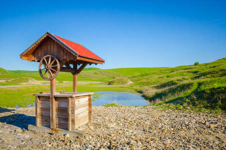 Traditional romanian wood well with roof in a green rural area with a pond and rock