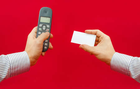 important phone call: Important contact us information with a hand holding a phone and another holding a contact business card with empty space for text getting ready to call