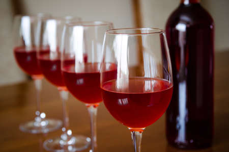 low light: Four red wine glasses with a bottle on the background and a shiny reflection with a low light melancolic mood and feel