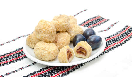 Plum dumplings woth prunes on a traditional romanian cloth Stock Photo