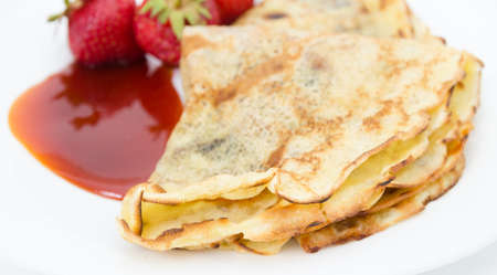 Close view of pancake crust with strawberries and jam on the background on white with a delicious tasty appetizing look