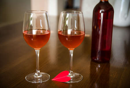 Love wine in two glasses and a bottle of red rose wine on the background with a dimm romantic look Stock Photo