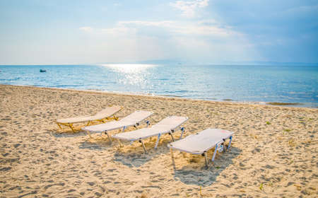 Four sunbeds on a sandy beach with a blue sea and sky on the background on a sunny summer day
