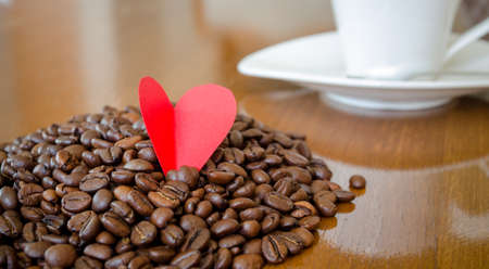 dimm: Coffee love and emotions suggested by a red heart placed on a pile of coffee beans with a cup on the background in a dimm romantic light