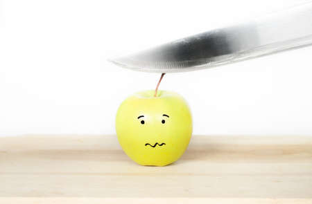threatened: Green yellow apple with a comic face being threatened by a knife blade getting ready to be chopped with a sad scared face on a wood board Stock Photo