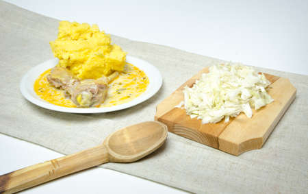 Traditional polenta with lamb stew and cabbage on a wood board