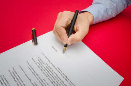 suggested: Sign here suggested by a business man hand signing a document on a red alerted background Stock Photo