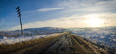unpaved road: Rural unpaved road waving over the hills and mountains on a snowy winter day at a bright melancolic sunset