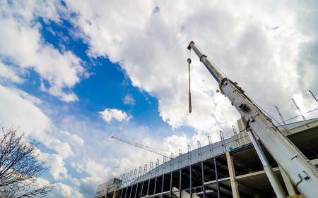 Industrial crane operating on a construction site with a building on the background and a blue sky with clouds on a sunny day