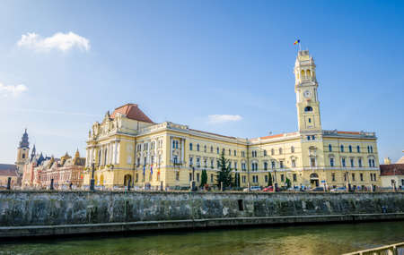 eclectic: Oradea, Romania - 26 October 2015: Oradea town Hall building built in a reinassance and eclectic style with the clock tower on the right and the Crisul Repede river in front in this beautiful city in the Transylvania region of Romania
