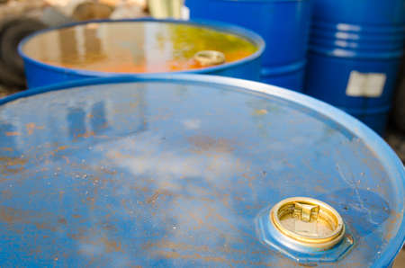 cilinder: Fuel oil barrels close view of nozzle with watter on them and rust starting to eat through the blue metal container suggesting toxic pollution, biohazard and ecology problems Stock Photo