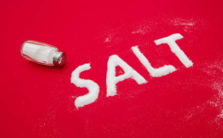 Salt health concerns, risk and problems suggested by the word written out of fine grinde white powder on a red background
