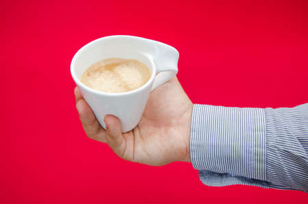 Hot cup of coffe in a business mans hand on a red dangerous background suggesting health risks, problems, issues and concerns due to high consumption Stock Photo