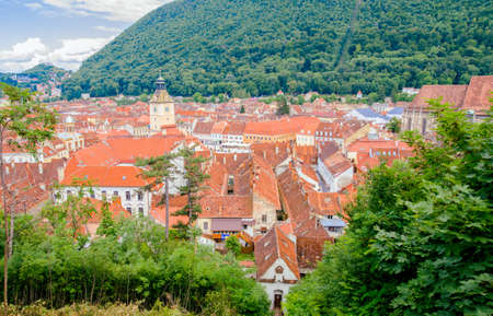 Brasov old historic medieval center view from above with the Council House Tower and the Black Church ands a lot of old buildings and roofs in this tourist attraction in the Carpathian Mountains, Romania. Soft filters applied Stock Photo