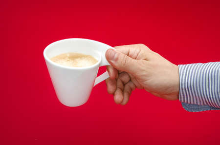 suggested: Dangers and health concerns of drinking too much coffee suggested by a white cup in a mans hand over a red alerted toxic background Stock Photo