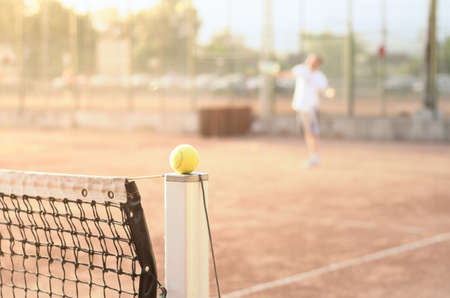Tennis player on a clay court with a ball on a net post in focus suggesting a tennis match with a warm sunny bright look with soft filter effects applied