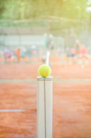 Tennis ball on a net post with a clay court on a bright warm sunny day with soft effects applied Stock Photo