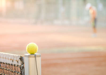 Tennis ball on a net post with a clay court on a bright warm sunny day with soft effects applied and a man serving on the background for the game Stock Photo