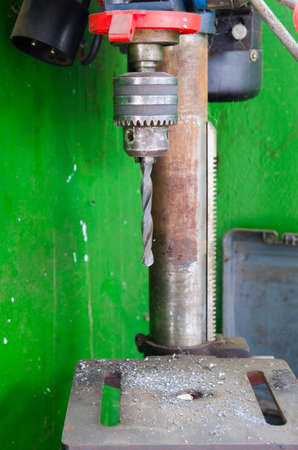heavy duty: Heavy duty industrial drill with metal pieces everywhere a dirty green background