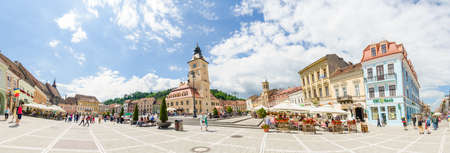 BRASOV, ROMANIA - 29 JUNE 2015: Brasov Sfatului (Council) Square  with the Town Hall or Council House, Black Church and other medieval historic buildings on a sunny summer day full of tourists in this wonderful Romanian Carpathian destination