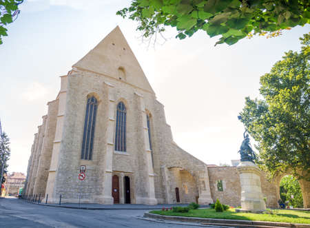 Reformed Church in Cluj Napoca city, Tranylvania region of Romania built in gothic style with reinassance elements with the statue of Saint George in front both historic monuments Stock Photo