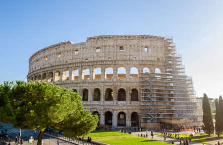 ROME, ITALY - 29 November 2015: Colosseum exterior with the scaffolding for restauration works and people walking near by this wonderful ancient monument