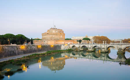 Rome, Italy - 1 December 2015: Castel SantAngelo, the Tiber River and the Aelius Pont Bridge on a warm sunset with lights all around and a blue sky. The castle of the pope and the bridge built by Hadrian. Editorial