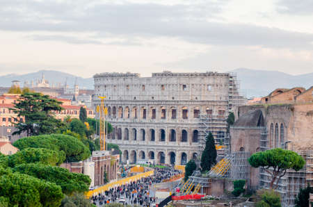 ROME, ITALY - 1 December 2015: View of the Colosseum and some othe ancient buildings being consolidated with lots of visitors around in this wonderful ancient destination