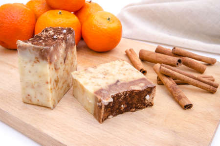 Traditional home made soap with orange and cinnamon aroma on a wood cutting board with a towel on the background