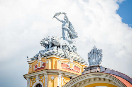 Statue on allegorical car pulled by lions on a tower at the Cuj-Napoca National Theatre and Opera House in the Transylvania region of Romania. A baroque rococo building in a close view with details of the harp in the middle of the roof Editorial