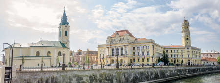 10 September 2016 - Oradea, Romania: City town hall and tower and the Saint Ladislau Baroque Roman Catholic Church and the Cri?ul Repede river