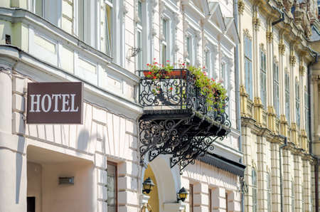 Hotel sign on an old building with a forged iron balcony filled with flowers and classic architectural details