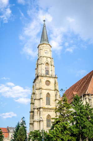 Saint Michael Church Tower in Cluj-Napoca city in the Transylvania region of Romania. Built in neo gothic architectural style with beautiful arched winbdows and a clock during the 15th century in the historic center of the city Stock Photo