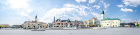 10 September 2016 - Oradea, Romania: Unirii Square with the Kovats House built in classicist architectural style and the tower from the Greek Catholic Christian Baroque Church, the Roman Catholic Baroque Church and the eclectic Town Hall
