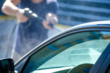 Man cleaning car at an auto shop with water vapor all over and a blue green reflection on the window Stock Photo