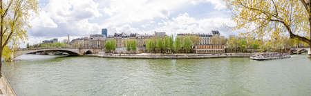 Paris, France - 1 April 2017: Panoramic view of the Seine river in Paris and old historic buildings on the back in this wonderful European city
